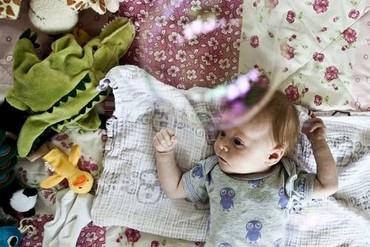 Baby der ligger på gulvet på tæppe omgivet af legetøj og babyklude