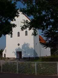 Ansgarkirken taget op mod indgangen med store træer i forgrunden.