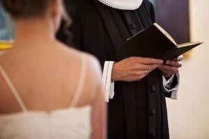 Præst og ryggen af konfirmand i forbindelse med konfirmation